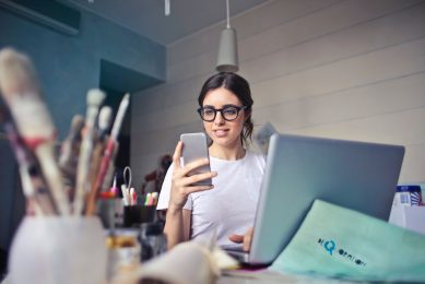 woman-in-white-t-shirt-holding-smartphone-in-front-of-laptop-914931